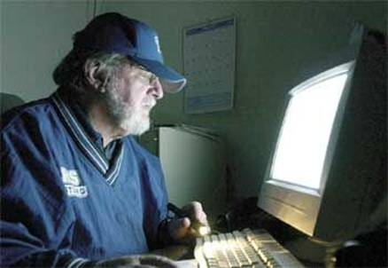Longtime Ramona Sentinel journalist Larry Littlefield, pictured working by the glow of a computor monitor and a small flashlight to meet his deadline after Santa Ana winds knocked out the power to most of downtown Ramona in January of 2002, died Saturday, April 16.